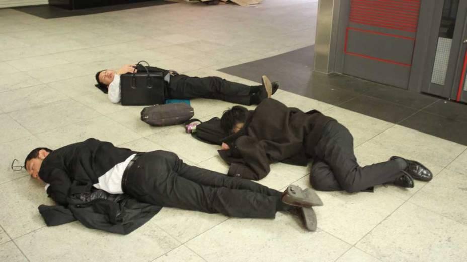 Japoneses dormem em estação de trem de Yokohama, Japão