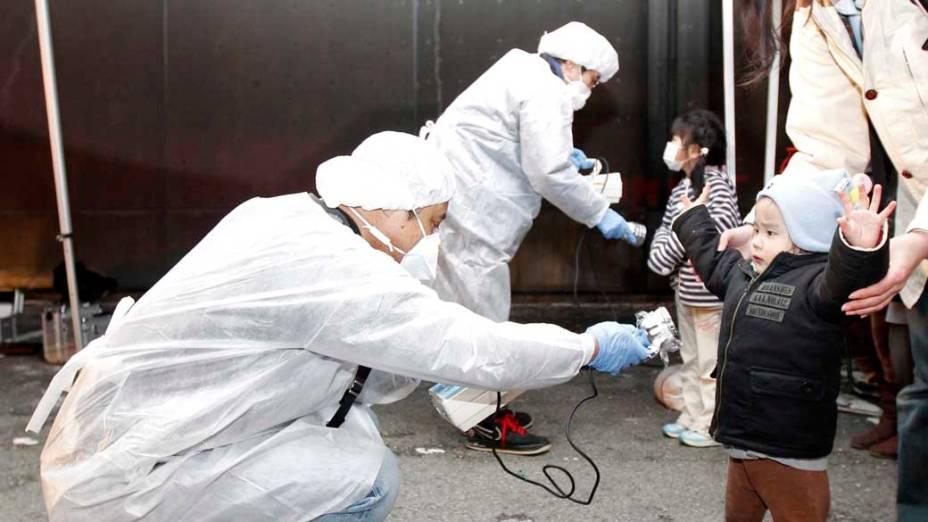Oficiais medem nível de radiação em crianças e famílias que evacuam a área perto da usina nuclear de Fukushima