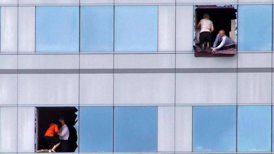 Trabalhadores tentam sair pelas janelas de um edifício, após o forte terremoto em Christchurch, Nova Zelândia