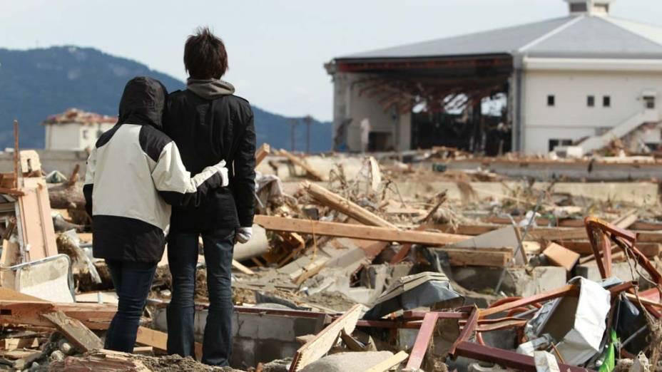 Irmãos observam a casa da família destruída em em Rikuzentakata, Japão