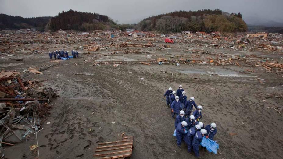 Policiais carregam corpos recuperados de escombros em Rikuzentakata, Japão