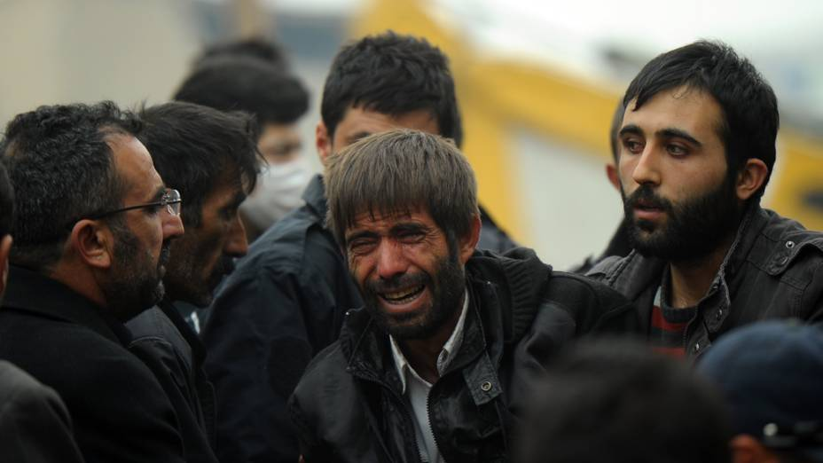 Parentes de vítimas do terremoto choram próximas a um prédio que desabou após um terremoto em Van, Turquia