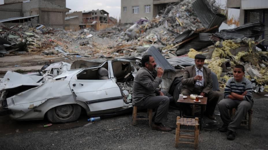 Moradores improvisam mesa nos escombros do terremoto em Ercis, na Turquia