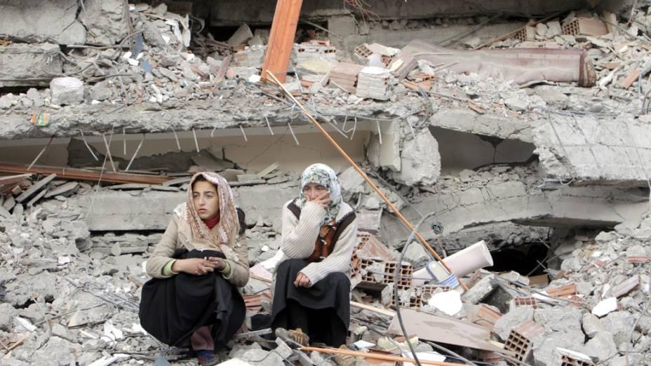 Moradoras sobre os escombros de um edifício em Ercis, Turquia