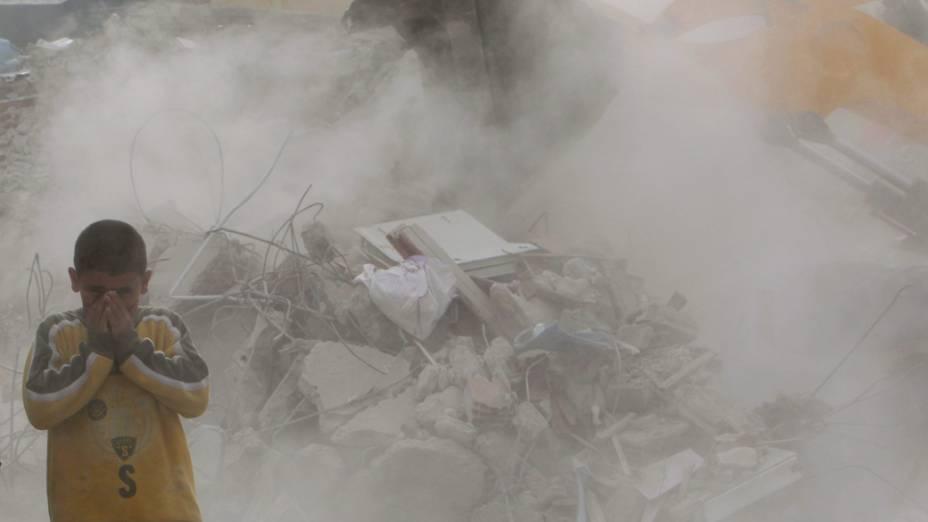 Garoto se protege da poeira durante remoção dos escombros em Ercis, na Turquia