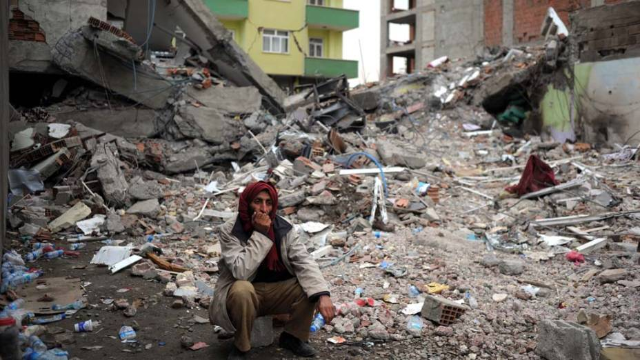 Morador entre escombros em Ercis, na Turquia