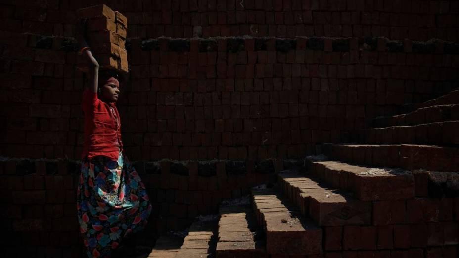 Jovem carrega tijolos para serem queimados na cidade de Karad, Índia