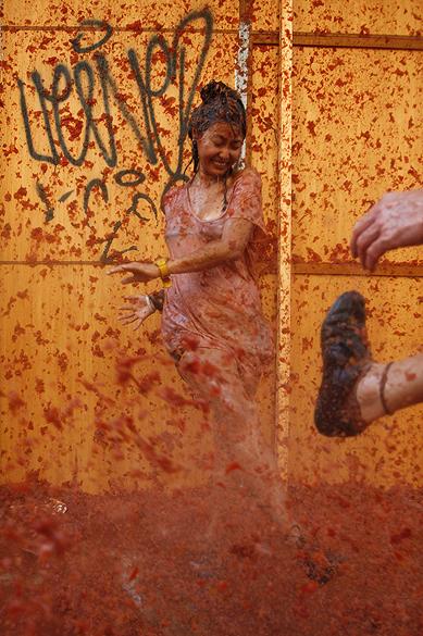 Mulher é alvejada por chuva de tomates na festa da Tomatina, em Buñol, na Espanha
