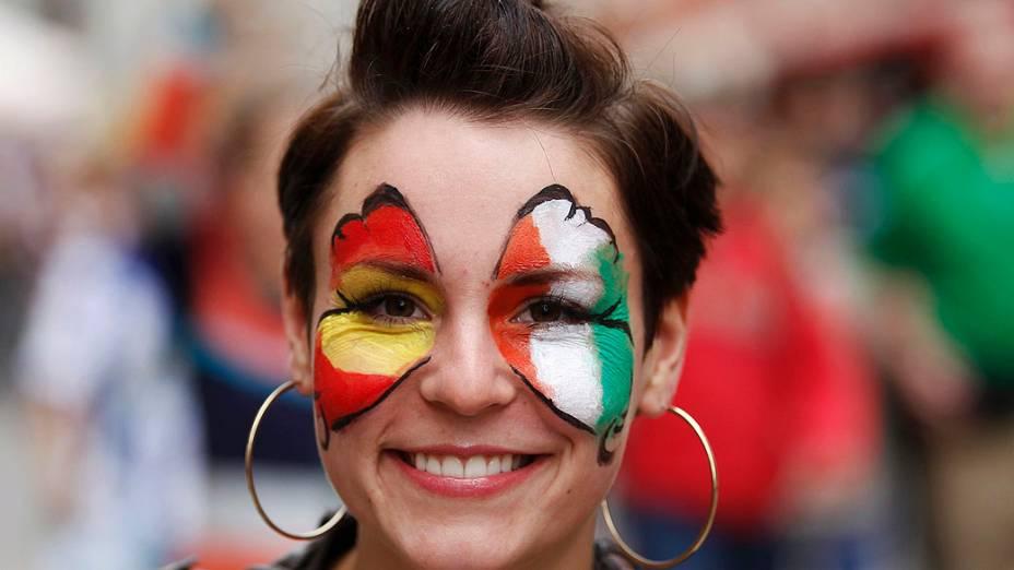 Torcedora com o rosto decorado com asas de borboleta em cores do time irlandês e espanhol, antes da partida de futebol Euro 2012