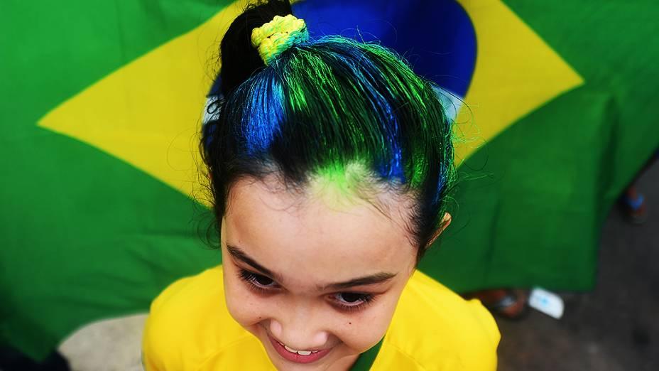 Criança pinta o cabelo com as cores da bandeira do Brasil
