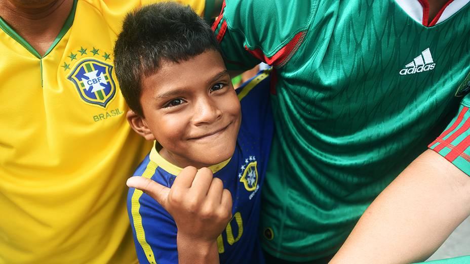 Menino veste a camisa do Brasil para recepcionar a seleção brasileira no Castelão, em Fortaleza