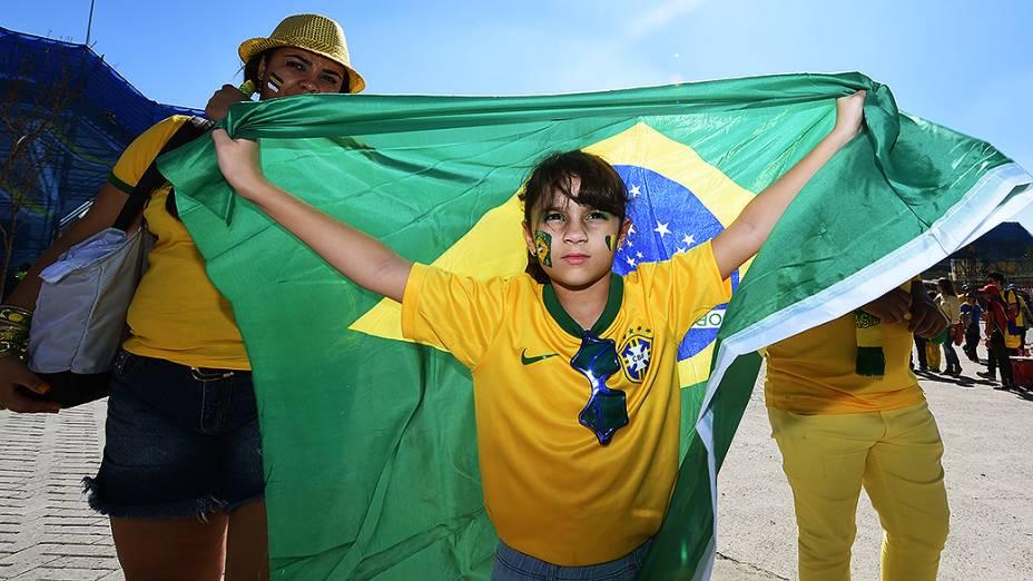 Menina levanta bandeira do Brasil em frente ao Itaquerão, em São Paulo