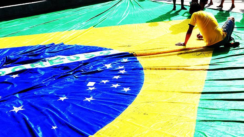 Torcedores assinam uma bandeira do Brasil antes do jogo contra a Colômbia no Castelão, em Fortaleza