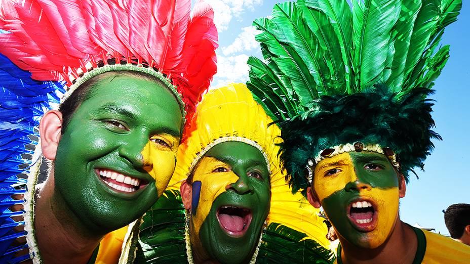 Torcedores pintam o rosto e usam cocar na cabeça antes do jogo contra a Colômbia no Castelão, em Fortaleza
