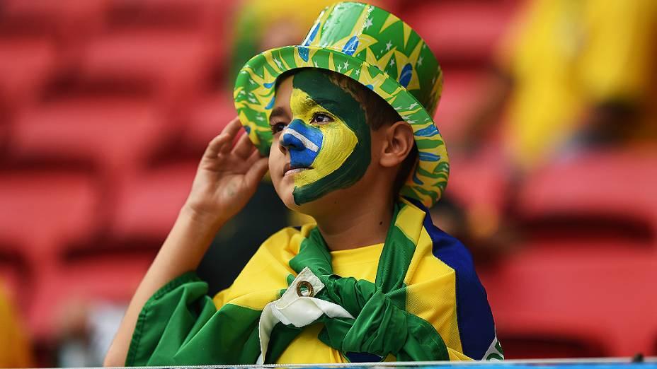 Menino aguarda o início do jogo entre Brasil e Camarões no Mané Garrincha, em Brasília
