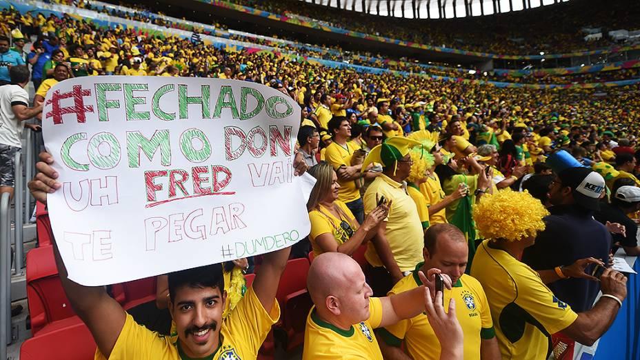 Torcedor brasileiro exibe cartaz no jogo entre Brasil e Camarões no Mané Garrincha, em Brasília