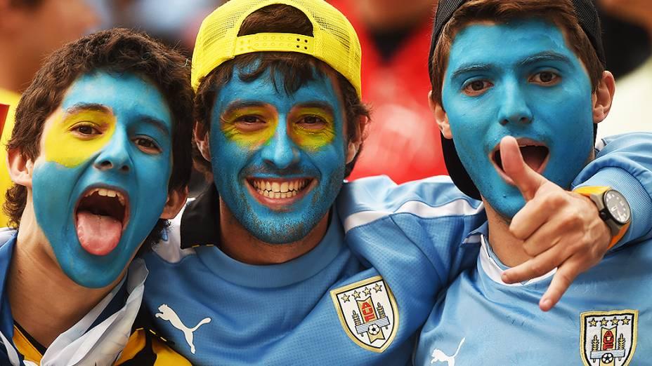 Torcedores do Uruguai pintam o rosto com as cores da bandeira do país, no Itaquerão