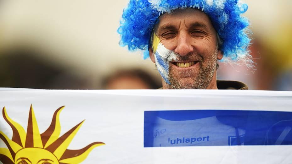 Torcedor do Uruguai segura a bandeira do país antes da partida contra a Inglaterra no Itaquerão, em São Paulo