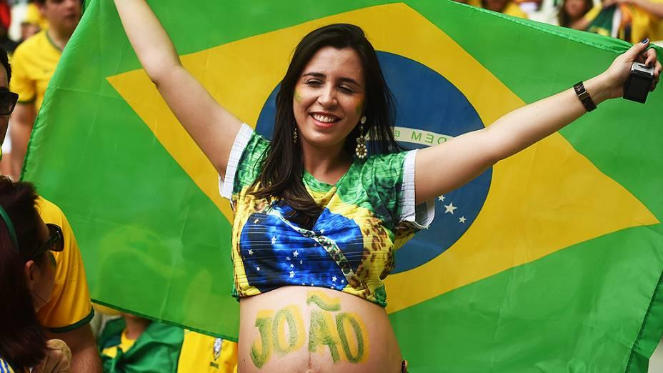 Torcedora do Brasil segura bandeira do país antes do jogo contra o México no Castelão, em Fortaleza