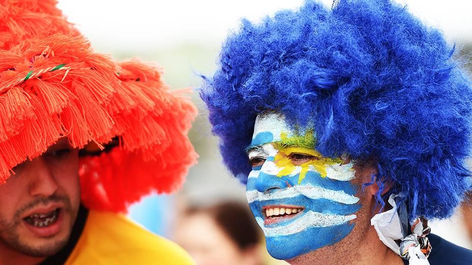 Torcedor pinta o rosto com a bandeira do Uruguai antes do jogo contra a Inglaterra no Itaquerão, em São Paulo