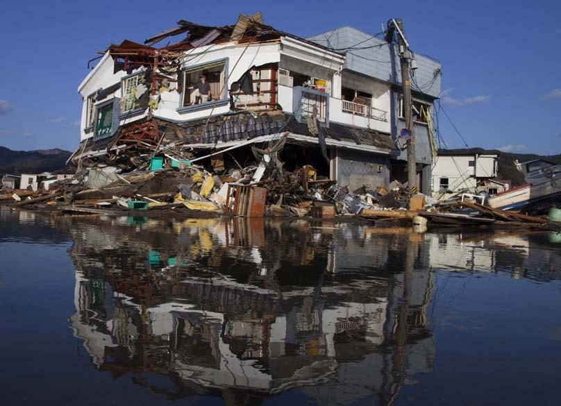 Toyoki Sugawara tenta resgatar alguns ítens em uma antiga loja de bebidas na cidade de Kesennuma, Japão