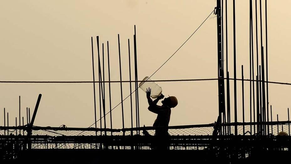 Trabalhador em construção na cidade de Nova Délhi, Índia