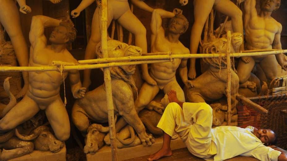 Funcionário descansa em fábrica de máscaras de argila em Calcutá, Índia