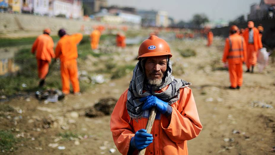 Trabalhadores afegãos limpam rio poluído, em Cabul, capital do Afeganistão