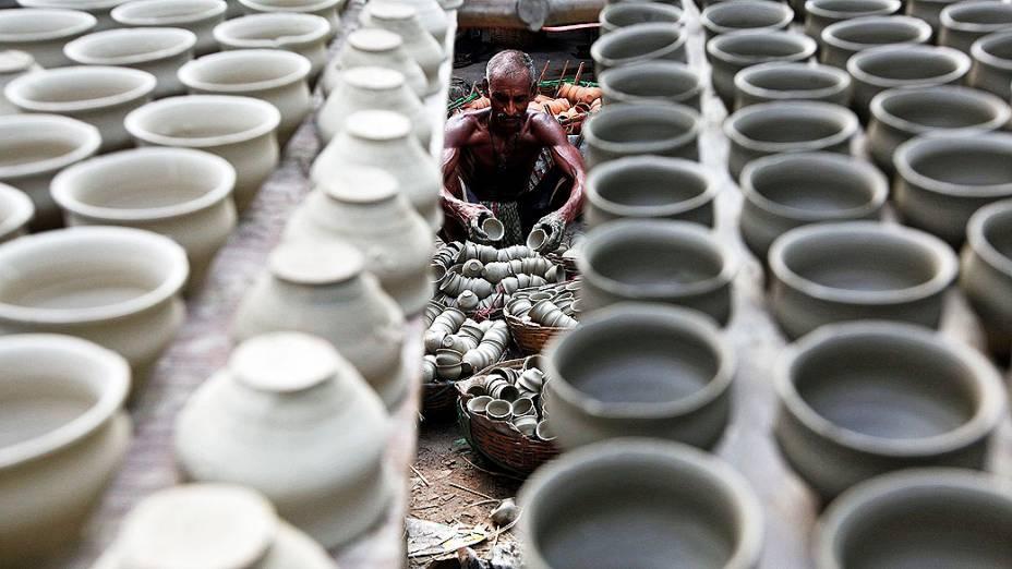 Oleiro coloca potes de barro em uma cesta para secar, dentro de uma oficina em Kolkata, na Índia