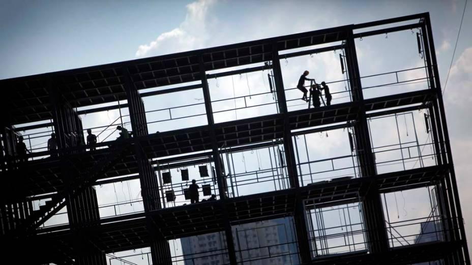 Homens trabalham na construção de um edifício na Cidade de Cingapura