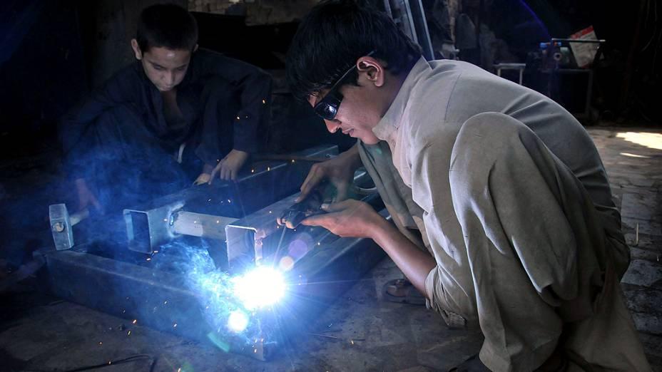 Crianças paquistanesas trabalhando em uma oficina em Peshawar, no Dia mundial de combate ao trabalho infantil
