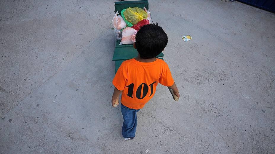 Criança hondurenha de dez anos de idade, transporta mantimentos em um carrinho de mão para um mercado na cidade Tegucigalpa