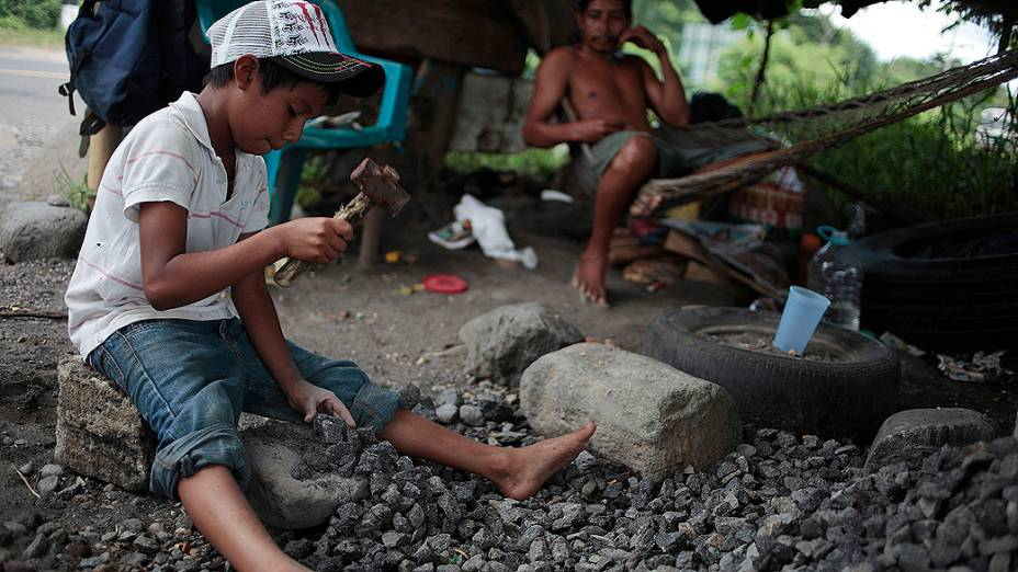 Menino de 9 anos usa martelo para quebrar pedras em estrada para Mazatenango, na Guatemala. O Dia Mundial Contra o Trabalho Infantil é comemorado nesta terça-feira