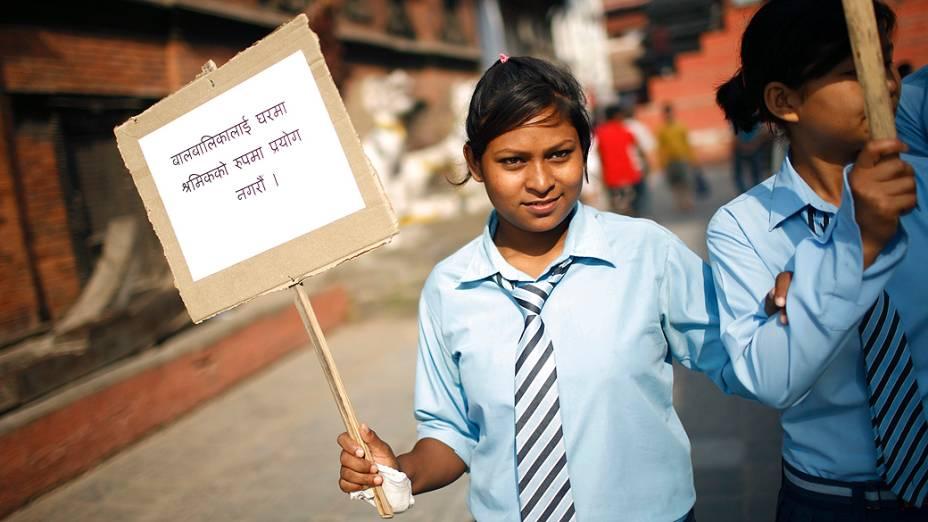 Estudante com um cartaz durante comício organizado para marcar o Dia Mundial Contra o Trabalho Infantil, em Katmandu, no Nepal