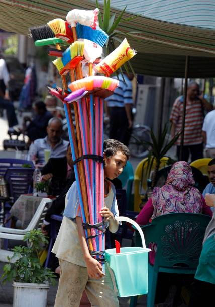Criança egípcia leva material de limpeza, no Dia Mundial Contra o Trabalho Infantil