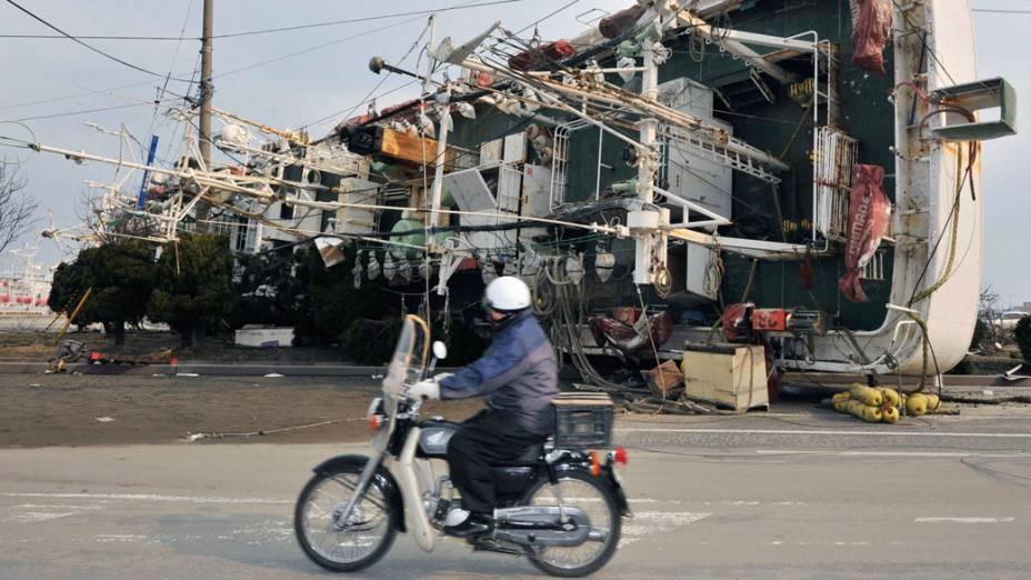 Homem passa de motocicleta próximo a barco arrastado pelo tsunami
