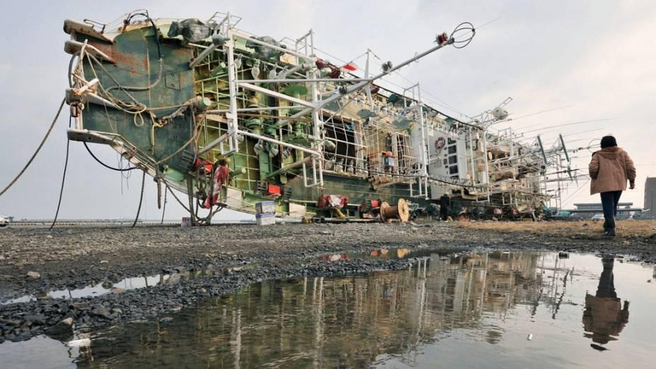 Japonês passa por restos de barco arrastado por tsunami na cidade de Hachinohe, no Japão