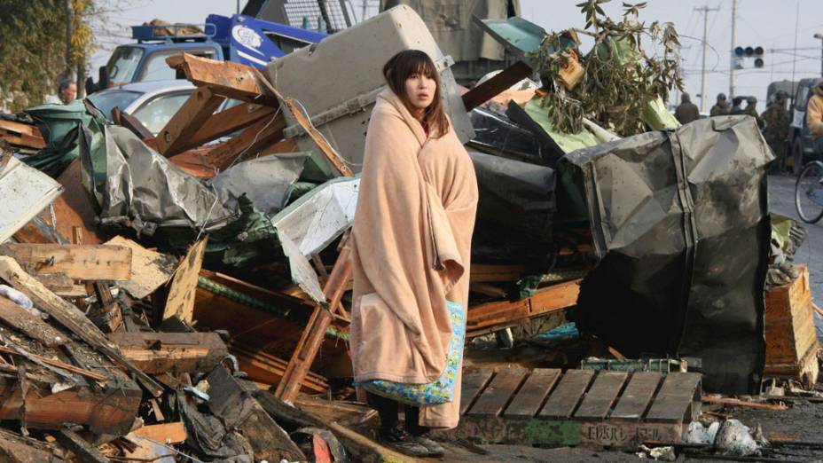 Japonesa observa restos das casas da cidade de Ishimaki, após terremoto e tsunami ter atingido a cidade
