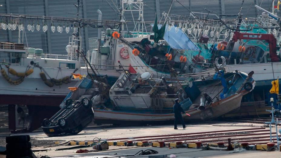Oficial caminha entre barcos e carros arrastados pelo tsunami que atingiu a cidade de Hachinohe, no Japão