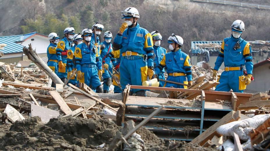 Equipe de resgate japonesa caminha por escombros das casas da cidade de Rikuzentakata em busca de sobreviventes