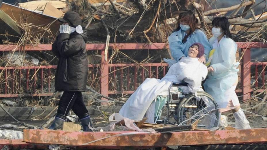 Enfermeiras transportam paciente durante a evacuação de hospital atingido por terremoto, na cidade de Otsuchi, no Japão