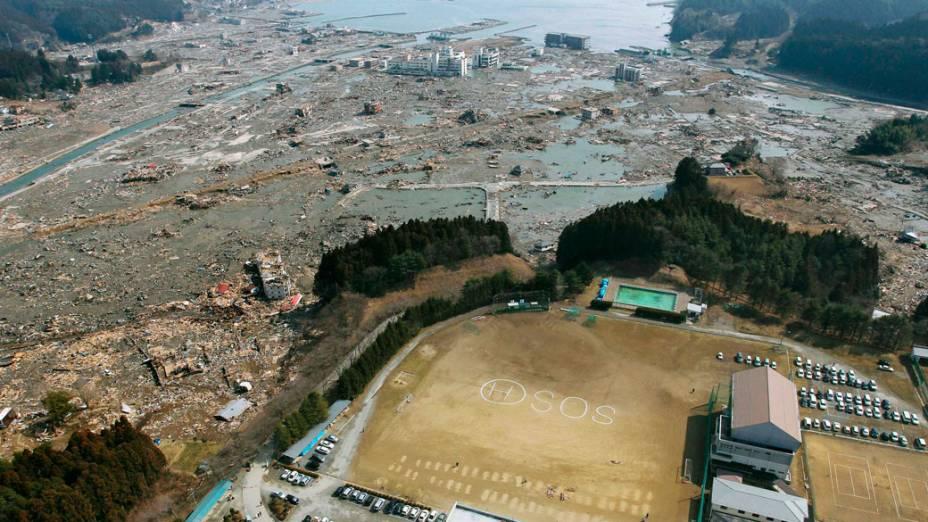 Sinal de SOS escrito em campo de futebol de escola japonesa, na região de Miyagi