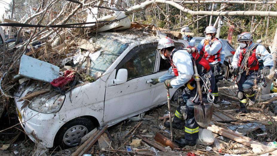 Equipe de resgate japonesa busca sobreviventes dentro de um carro arrastado pelo tsunami