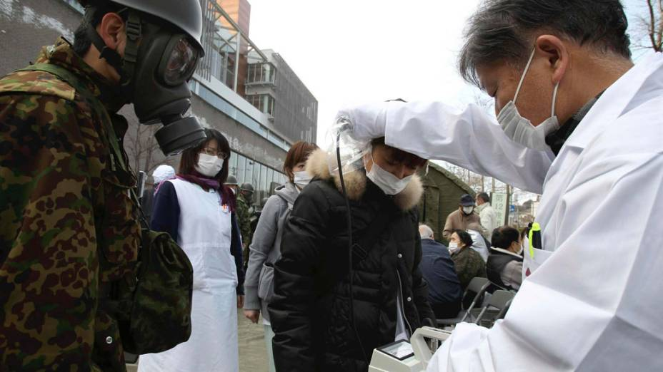 Oficial mede nível de radiação em jovem que evacuou a área perto da usina nuclear de Fukushima, no Japão