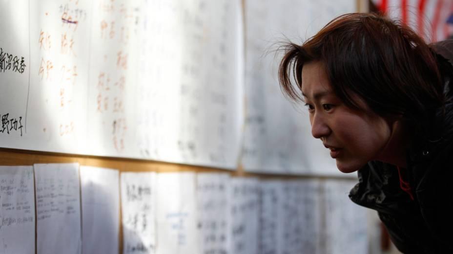 Sobrevivente procura pelo nome de familiares em painel montado na cidade de  Rikuzentakata