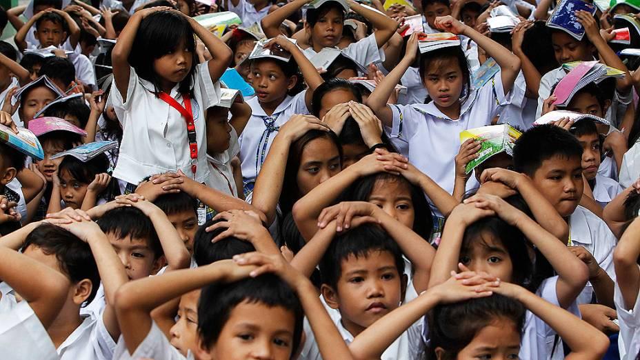 Estudantes filipinos cobrem suas cabeças em simulação de terremoto em escola de Manila