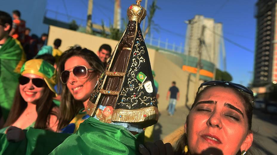 Torcedoras carregam uma imagem de Nossa Senhora Aparecida durante o treino do Brasil no Castelão, em Fortaleza