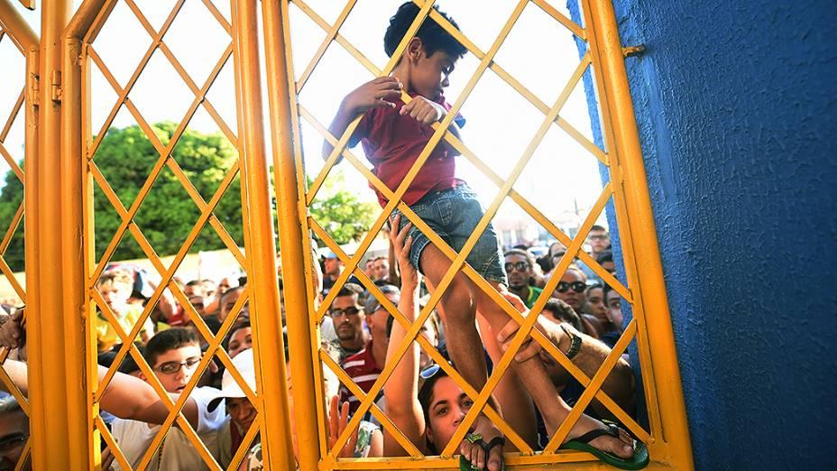 Menino sobe no Portão da Arena Castelão durante o treino do Brasil, em Fortaleza