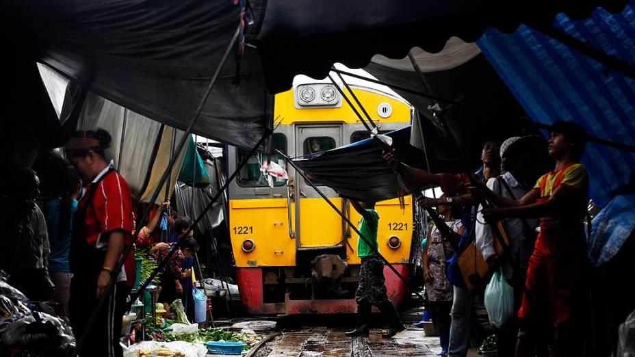 Feirantes retiram frutas e toldos para trem passar em Maeklong, na Tailândia. A feira precisa ser desmontada oito vezes ao dia para a passagem dos vagões