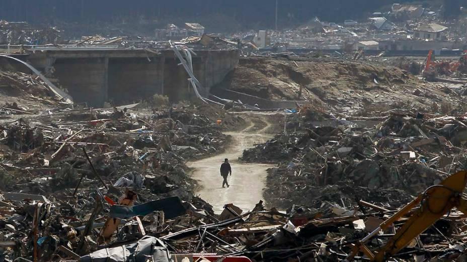 Homem caminha em meio a devastação pelo tsunami em Rikuzentakata, Japão